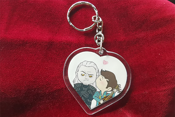 Geralt and Jaskier from The Witcher sharing a Geraskier kiss in a heart shaped charm