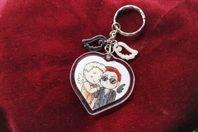 Heart shaped Ineffable Husbands charm with resin wings showing Aziraphale and Crowley from Good Omens